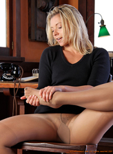 Foxy sec Nicole teases with her pantyhosed legs and feet stripping in the office