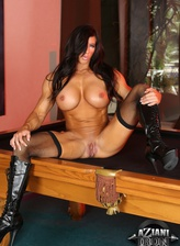Strong pool player Angela Salvagno flexing her muscles in black holdups and boots