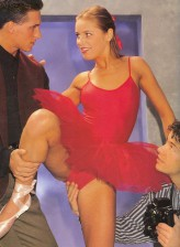 Retro ballerina in a red tutu spreads her slim legs in pointes dancing on a cock