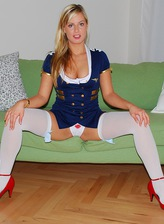 Blonde girl in air hostess uniform and white bow graced stockings