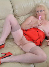 Aged English lady Claire Knight toy plays in her tan nylons with bright red corset, panties & pumps