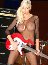 Super busty rock babe playing guitar in her fishnet bodystocking
