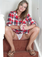 British milf Louise Pearce in shiny holdups pulls her panties down on the stairs