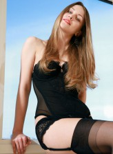 Fascinating erotic beauty Violet gets rid of her black corset, garter belt and nylons by the window