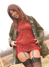 Unabashed chick flashes her gartered stockings and pussy outdoors