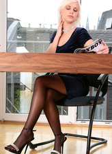 Hot office blonde Lola N. flashes boobs and pussy as she plays with her pantyhosed toes on the desk