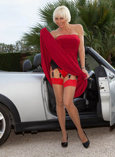 Blonde English lady Jan Burton flashes the tops of her red seam-n-top stockings in the car
