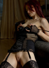 Fiery redhead teases with her fashion stockings strapped to a showy black corset