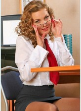 Curly blonde secretary boasting seamed stockings and red pumps