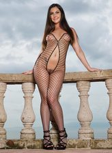 Brittany Shae clad in her fence net bodysuit and heels stuffs a blue butt plug