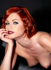 Foxy redhead strips to black holdups to show her pussy close up