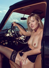 Sexy blonde gets topless and opens endless stockinged-clad legs in a vintage car