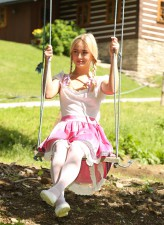 Blonde teen doll Cayla A swings in the sun in her white tights before frigging her pussy by the tree
