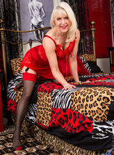 Red-hot British blonde granny Margaret Holt spreads legs on the bed in her sultry two-tone stockings