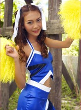 Asian cheerleader Vicky Pareemon parts booted legs outdoors to show her goods