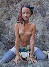 Tender redhead filmed in her blue footless opaques among the rocks by the sea