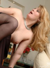 Dolled-up milf reveals her black nylons scoring with a young guy