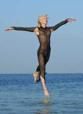 Epic blonde nude Natali F does acrobatics in the river in her wet sheer bodysuit