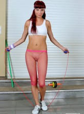 Sporty redhead exercising in her provoking pink fishnet knickerbockers showing it all