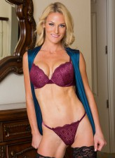 Blonde cougar Sydney Hail strips to her sexy burgundy lingerie and black holdups