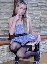 Sugary blonde in black fully-fashioned stockings fools with a toy