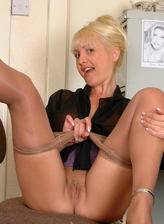 Provokingly dressed British mature Wendy Jayne lowers her sheer pantyhose for office toy play