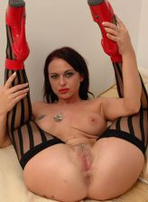 Sexy Australian brunette Elizabeth Michelle Lawrence gets naughty in stripy hold-ups and red spike heels