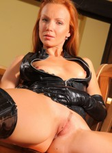 Redheaded mistress Alisson in tight fitting leather undies and gloves opens her booted legs