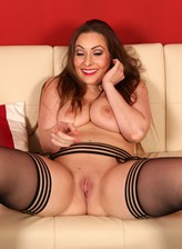 All dolled-up busty Sophia Delane strips to nylons and platform heels for a wank