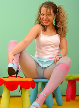 Ponytailed mischief wearing pink knee-highs over her glossy hose