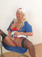 Horny mature nurse Wendy Jayne strips to red lingerie & black nylons for a dildo