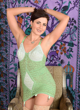 Cute UK milf Helena Price wears a green lace corset with attached nude stockings to show her bush