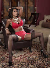 Black Diamond Jackson strips to her fiery red lingerie and ebony nylons in the dark leather armchair