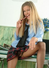 Naughty schoolgirl in a tartan skirt and black pantyhose strips to her tie exposing big boobs