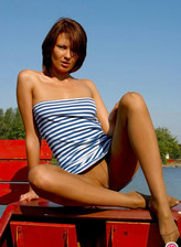 Teasing young girl in pantyhose poses near a park lake