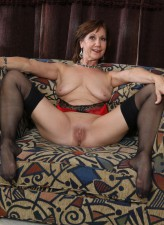 Smart-looking mature lady Demi strips to her black stockings with a red garter for her rubber lover