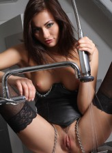 Dangerous beauty Michaela Isizzu in a chain-trimmed leather corset and raunchy black fishnets in the kitchen