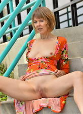 US milf Jamie Foster flashes her ripe boobs and pussy outdoors opening long slim legs in high heels