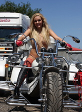 Topless blonde spreading legs in red fishnets and strapped up boots on 3-wheeled bike