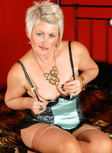 Dolled-up UK milf Sally Taylor flashing goodies in lacy bustier and tan stockings