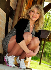 Hot milf showcases her legs encased in glossy suntan tights and sneakers in the sun outdoors