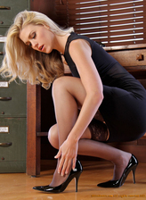 Blonde Shayla adjusts her stockings in the office before spreading legs on a desk
