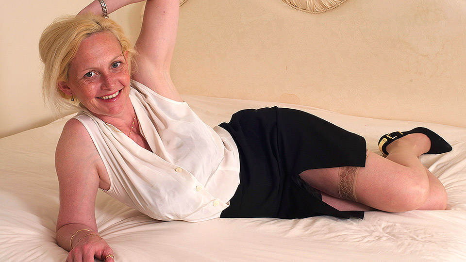 Blonde British mature in sheer holdups plays with her ripe boobs and pussy on the bed
