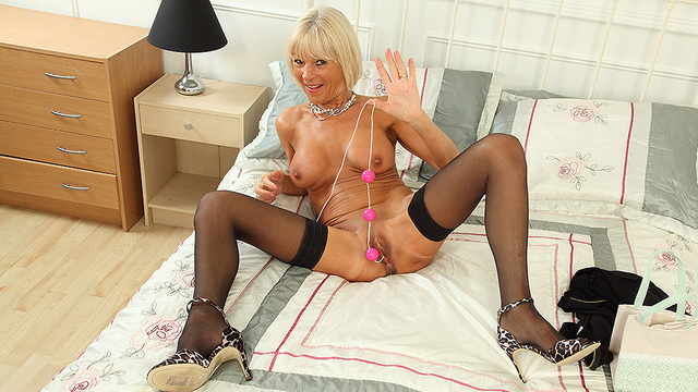 Skinny British mature blonde Elaine Mac in black stockings toying her pussy