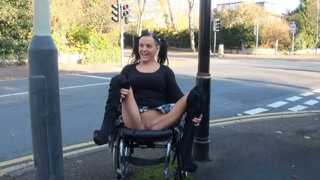 Wheelchair-bound Brit Leah Caprice flashes by the busy road parting booted legs