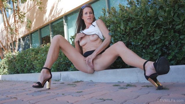 Pantieless milf Sofie Marie spreads her long high heeled legs frigging in public