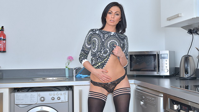 Stunning British milf Roxanne Cox with shapely legs encased in black opaques plays in the kitchen