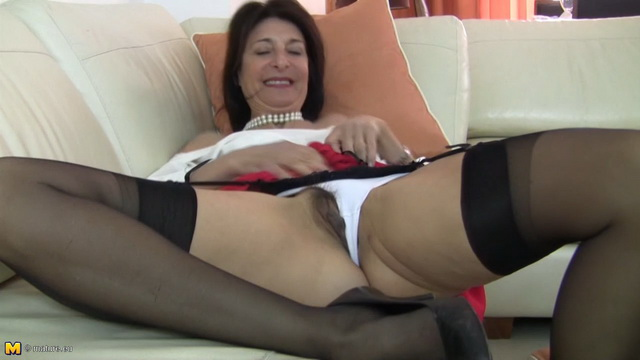 Smart mature Emanuelle shows her naughty side toying her bush in black stockings