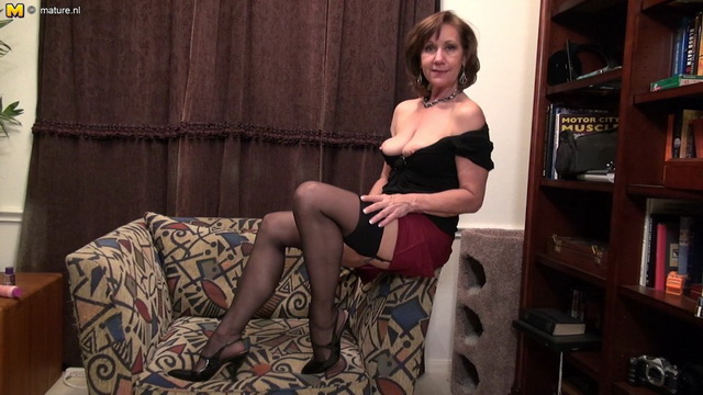 Elegant mature Demi gets in the mood for solo dildo play stripping to her sultry gartered stockings