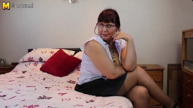 Buxom British mature lady in glasses Alexa exposes her bright lingerie and tan stockings on the bed